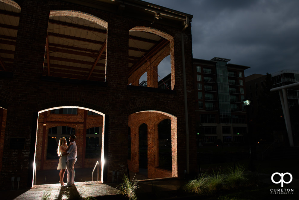 Epic photo of a couple standing in an opening of the Wyche Pavilion during an engagement session in downtown Greenville,SC.