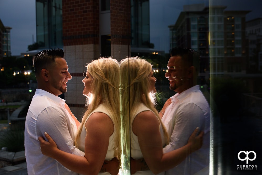 Couple smiling in their reflection during an engagement session in downtown Greenville,SC.