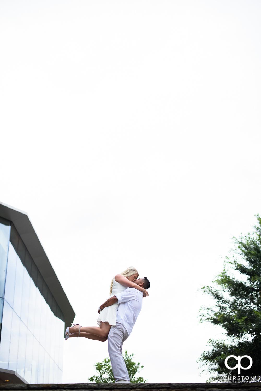 Groom lifting his bride.