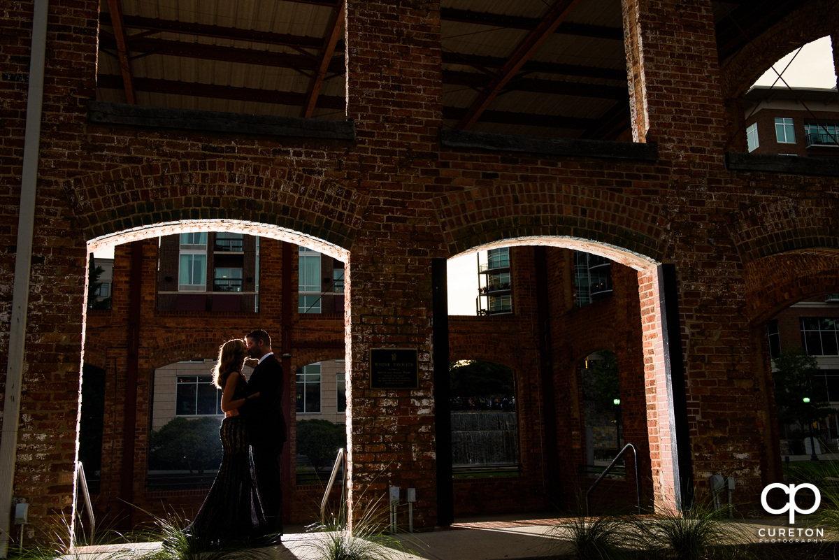 Engaged couple kissing in the window of the Wyche Pavilion behind Larkin's on the River.