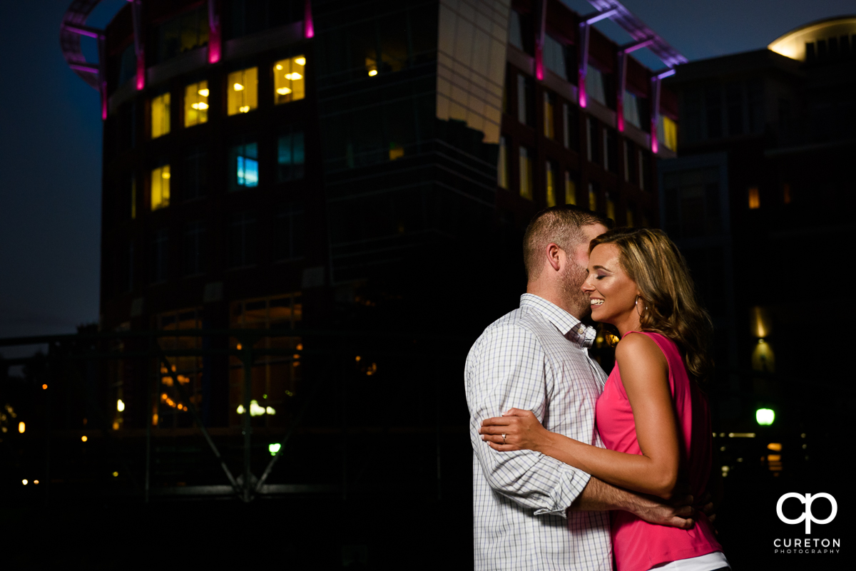 Engagement photo of a couple dancing with the downtown Greenville skyline in the background.