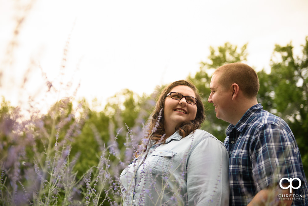 Future Bride and Groom smiling at each other in Falls Park during their engagement session with their puppy.
