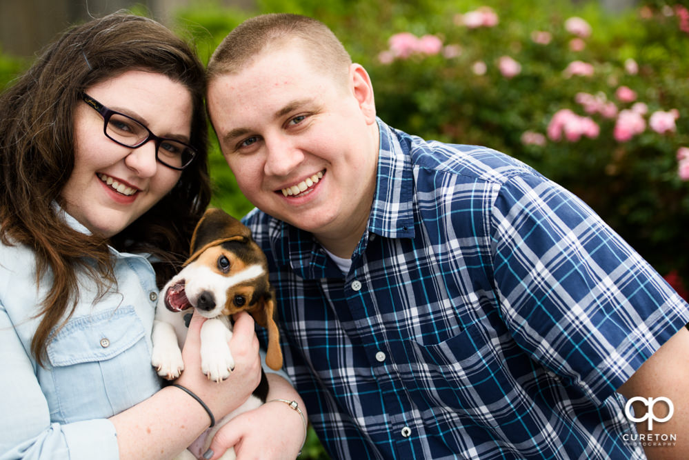 Couple smiling with a beagle during their engagement session with their puppy in downtown Greenville.