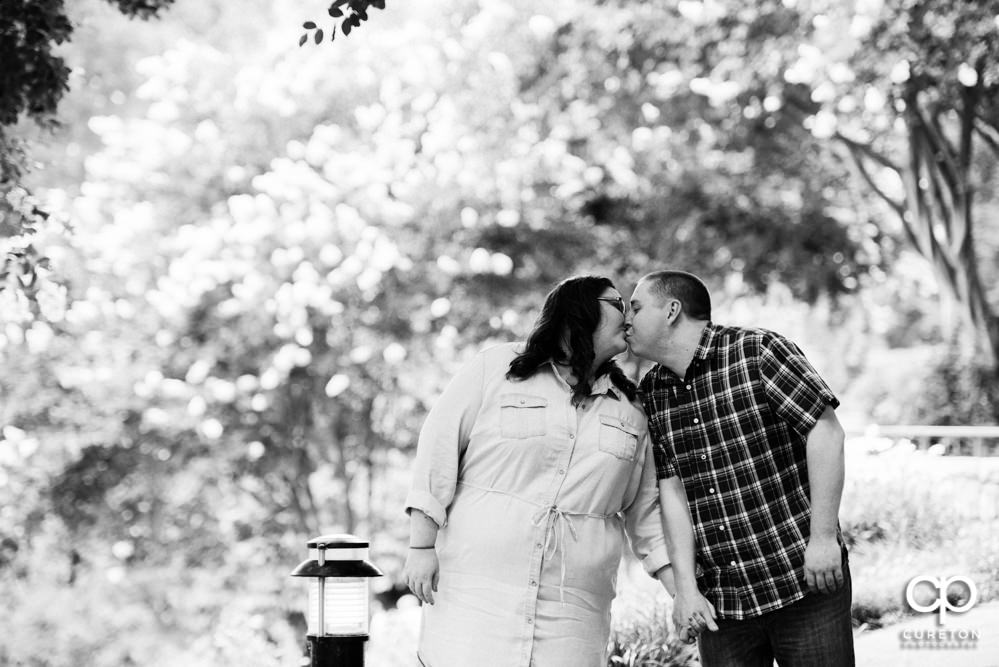 Black and white photo of a couple kissing each other in Falls Park.