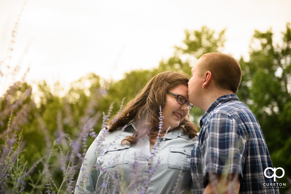 Man kissing his fiancee on the forehead during their engagement session with their puppy.