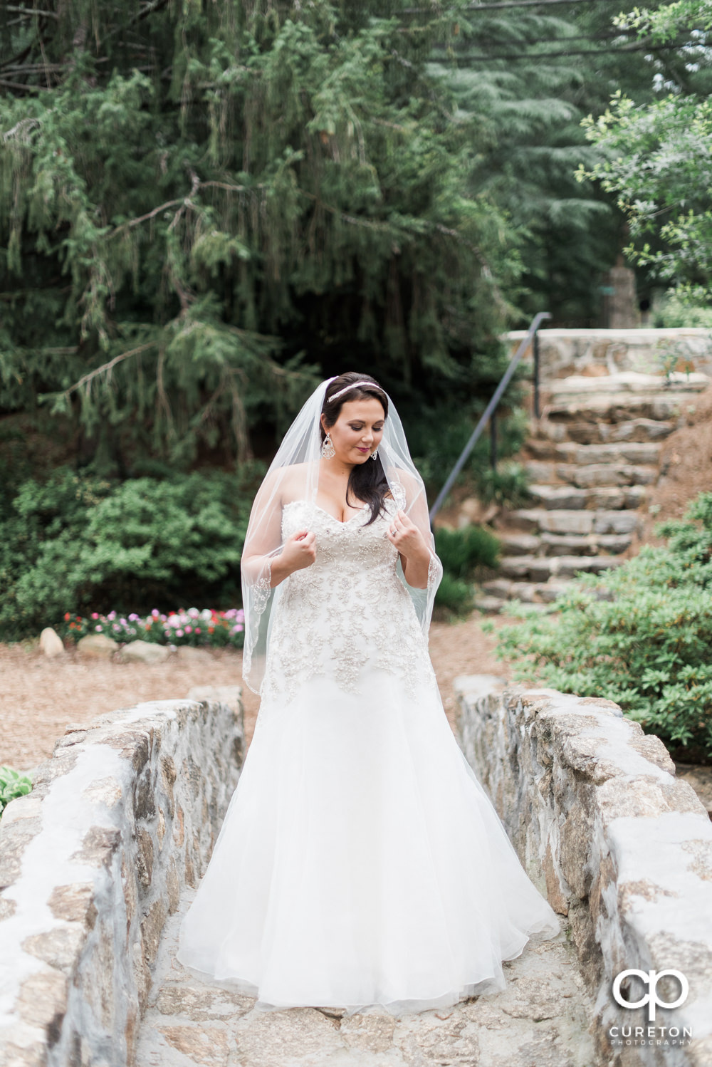 Bride holding her veil on the stone bridge at the rock quarry in Greenville.