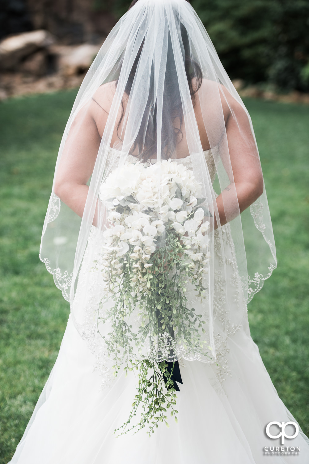 Bride holding her flowers behind her back.
