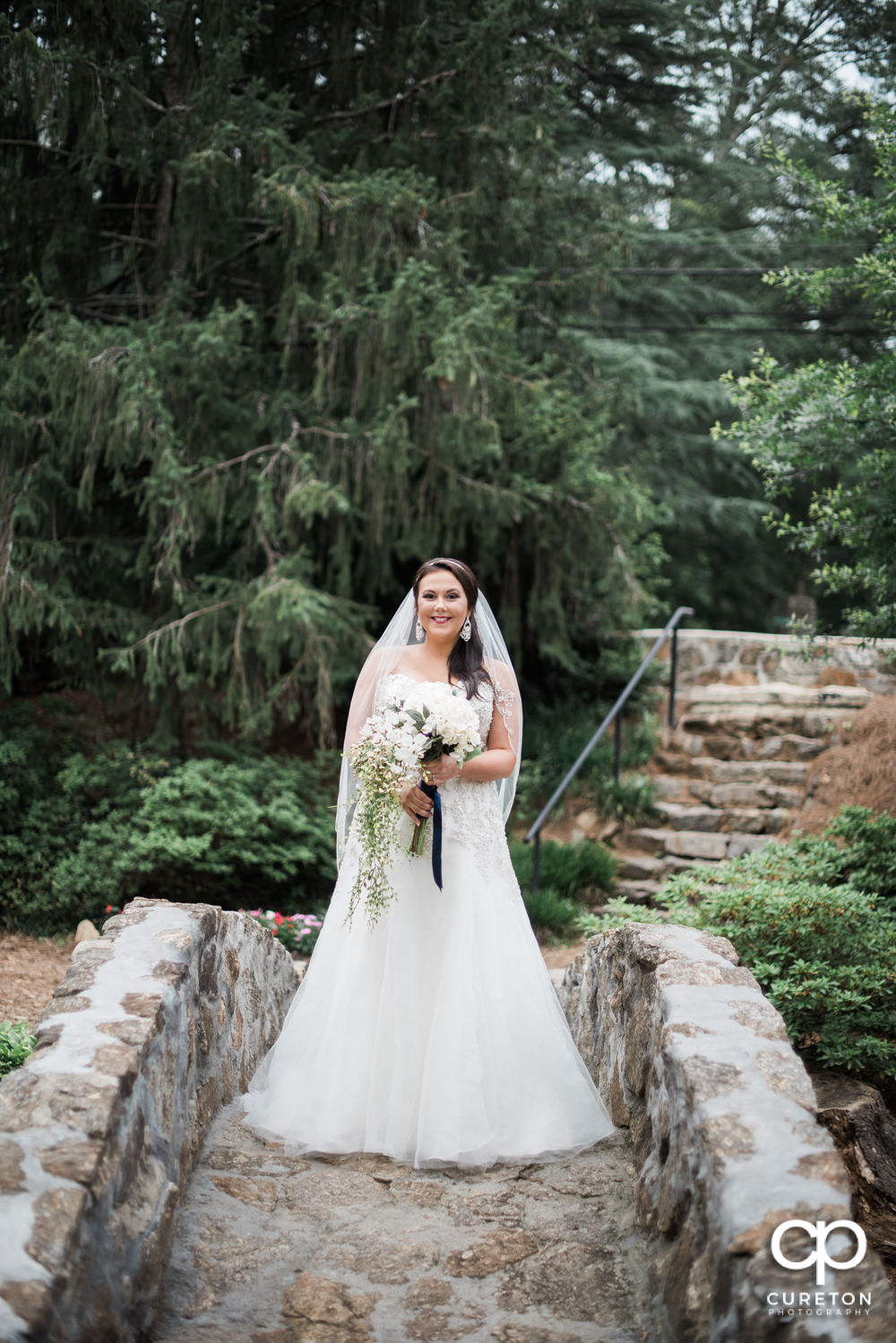 Bride standing on the stone bridge over the Reedy River at the Rock Quarry Garden in downtown Greenville.