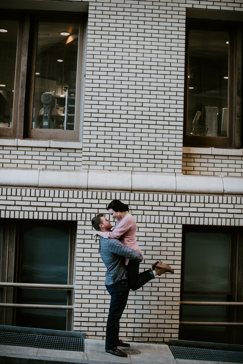 Groom lifting his bride outside of the Westin Poinsett in downtown Greenville during an engagement session.