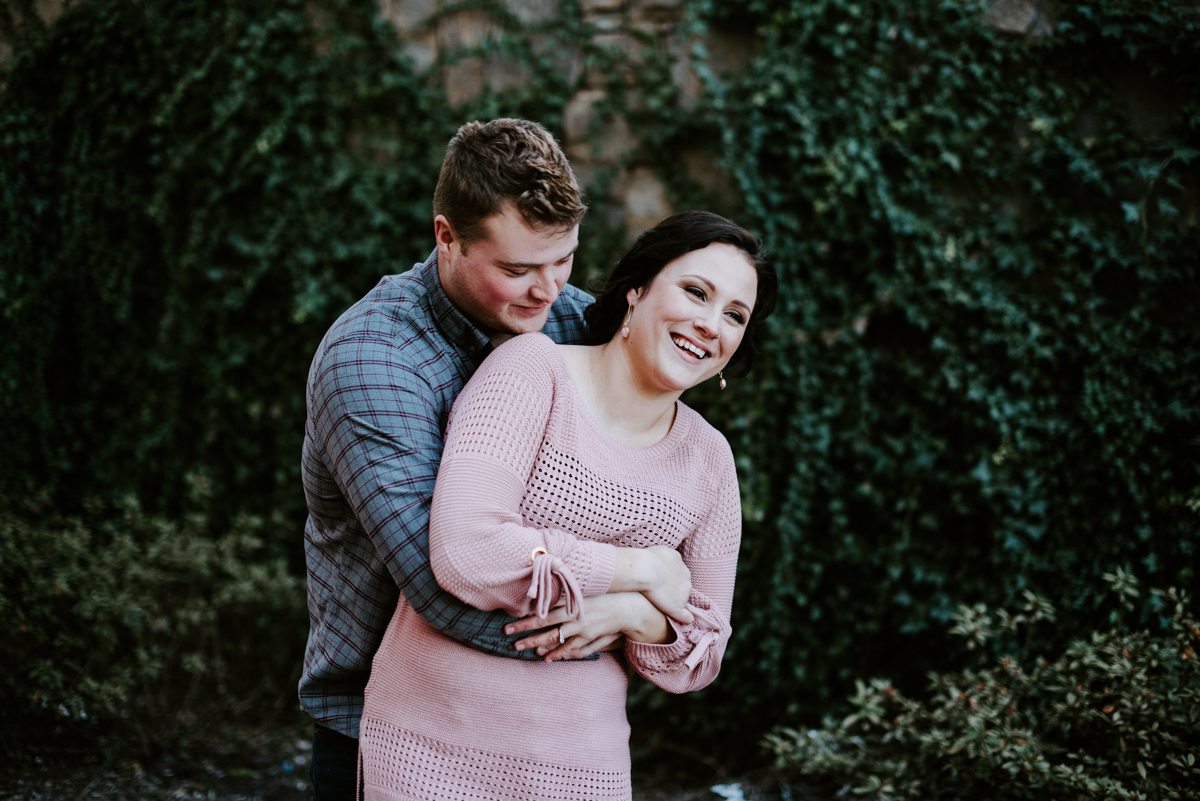 Bride and groom laughing during an engagement session in January.
