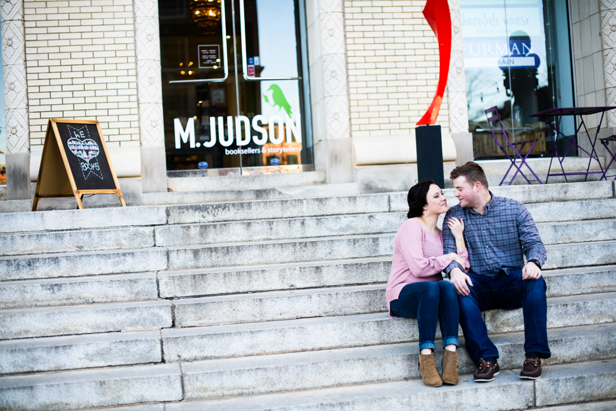 Bride and Groom sitting on the steps in downtown Greenville during their engagement session.
