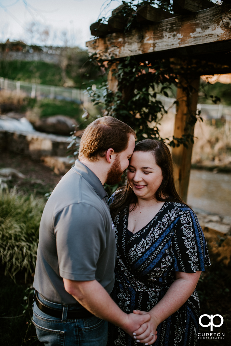 Future bride and groom snuggling near the Reedy RIver during a Greenville,SC park engagement session.