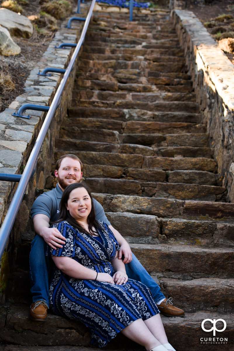 Engaged couple sitting on some rock steps during a Greenville,SC park engagement session.