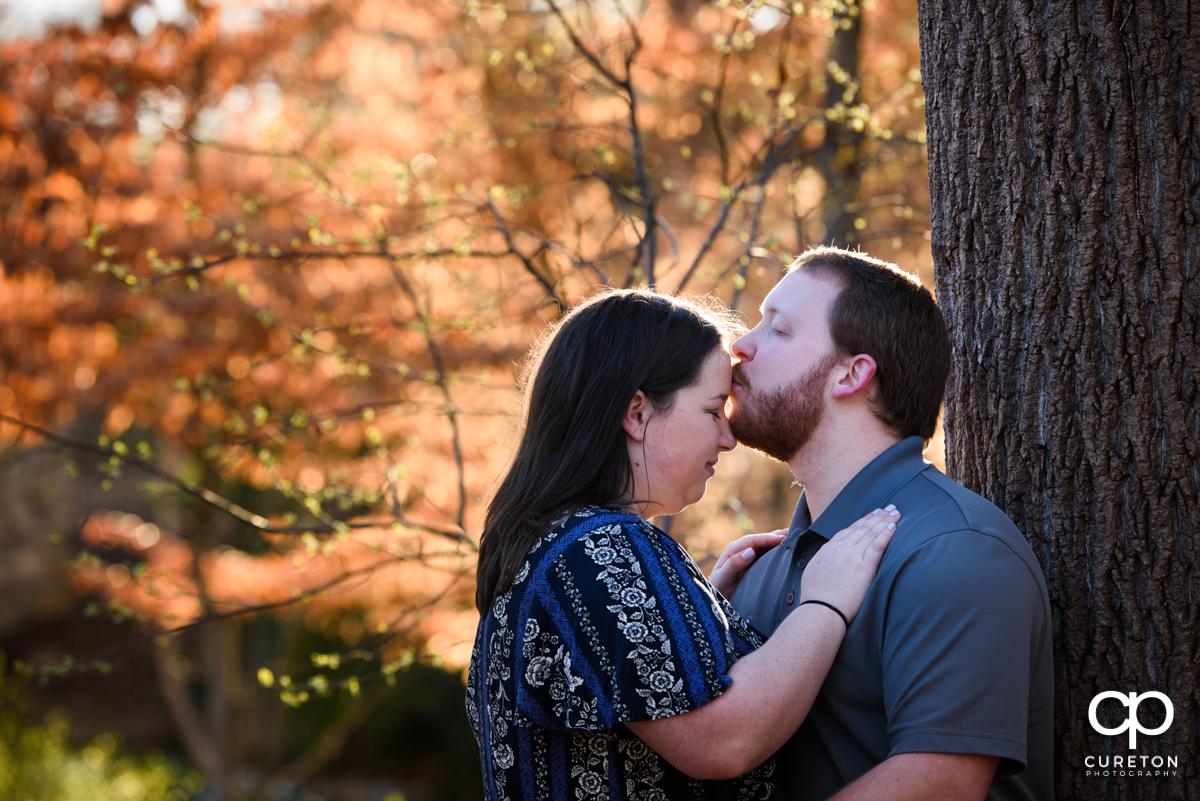 Man kissing his fiancee on the forehead during a Greenville,SC park engagement session.