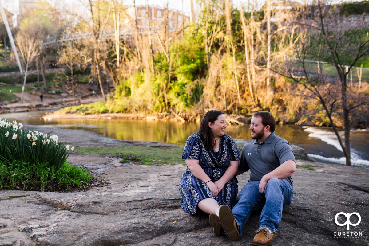 Engaged couple sitting on a rock near the Reedy river.