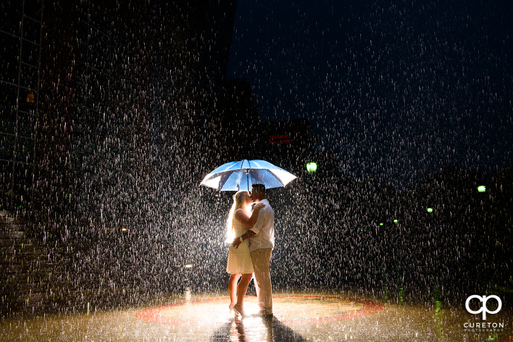 Future bride and groom standing in the rain in the middle of downtown Greenville SC during their engagement session