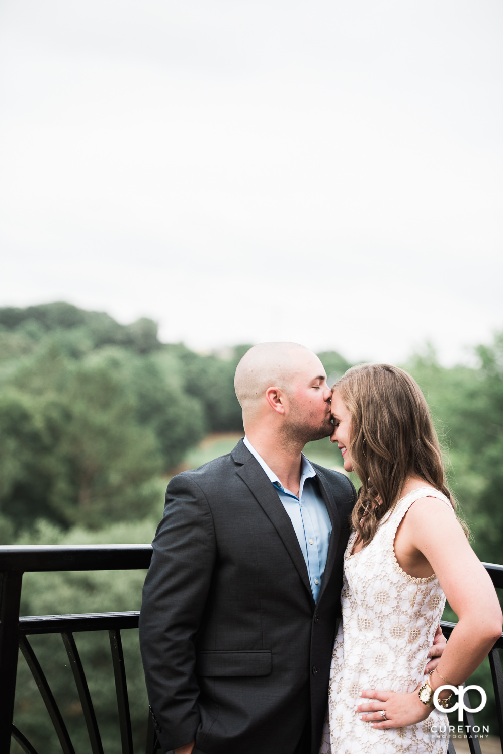 Groom kissing his bride's forehead at their wedding rehearsal dinner at the Thornblade Country Club in Greenville , SC .