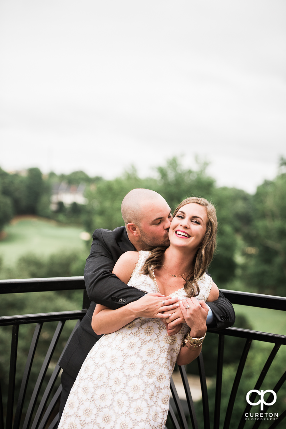 Groom kissing his bride at their wedding rehearsal dinner at the Thornblade Country Club in Greenville , SC .