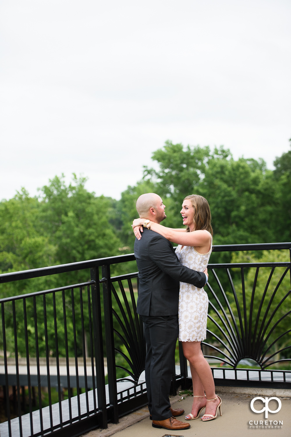 Engaged couple hugging at their wedding rehearsal dinner at the Thornblade Country Club in Greenville , SC .