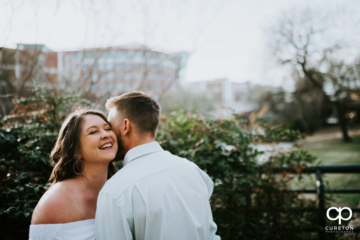 Man whispering in his wife'e ear in a downtown Greenville,SC park during an anniversary session.