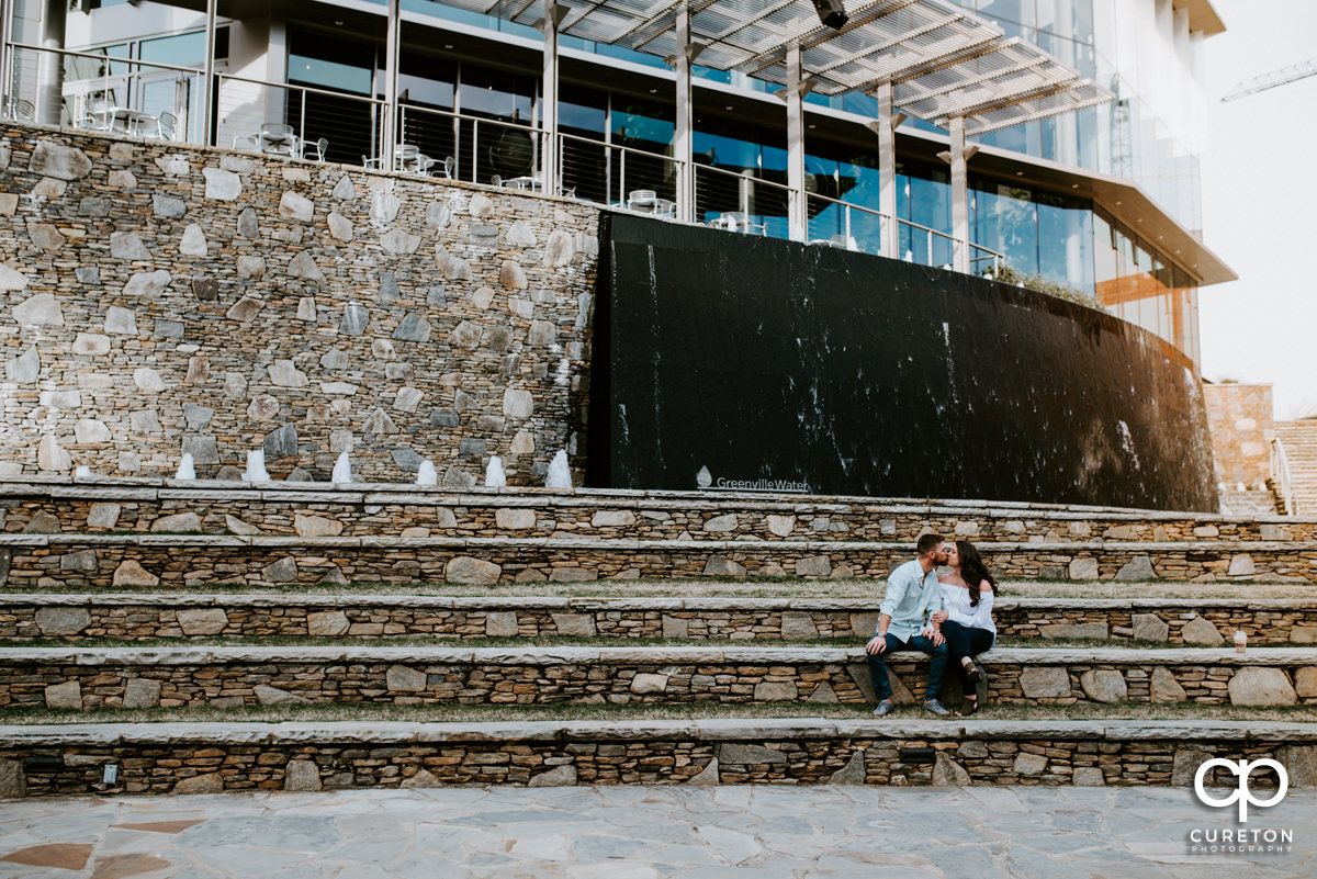 Husband and wife sitting on some steps behind the Peace Center during a Greenville,SC anniversary session.