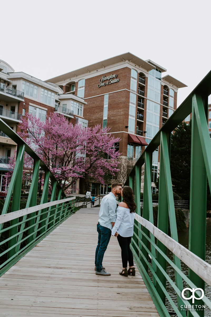Groom kissing his bride on a bridge during a Greenville,SC anniversary session.
