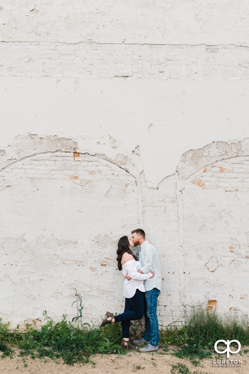 Man kissing his wife while dancing in front of a white wall during a Greenville,SC anniversary session.