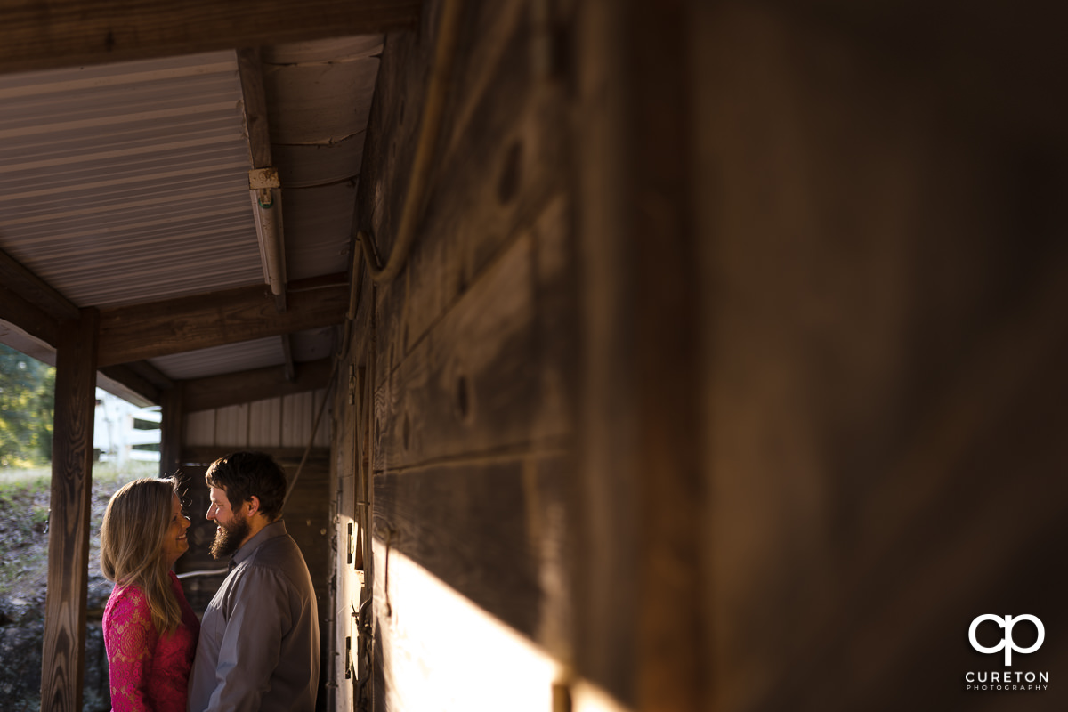 Bride and groom standing outside of a horse stable during a summer engagement session in Greer,SC.