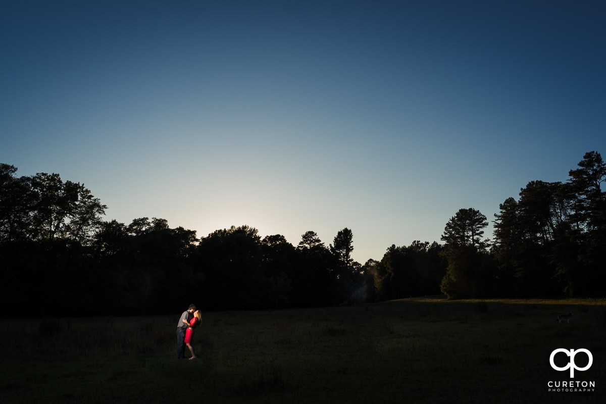 Engaged couple in a field at sunset during a summer engagement session in Greer,SC.