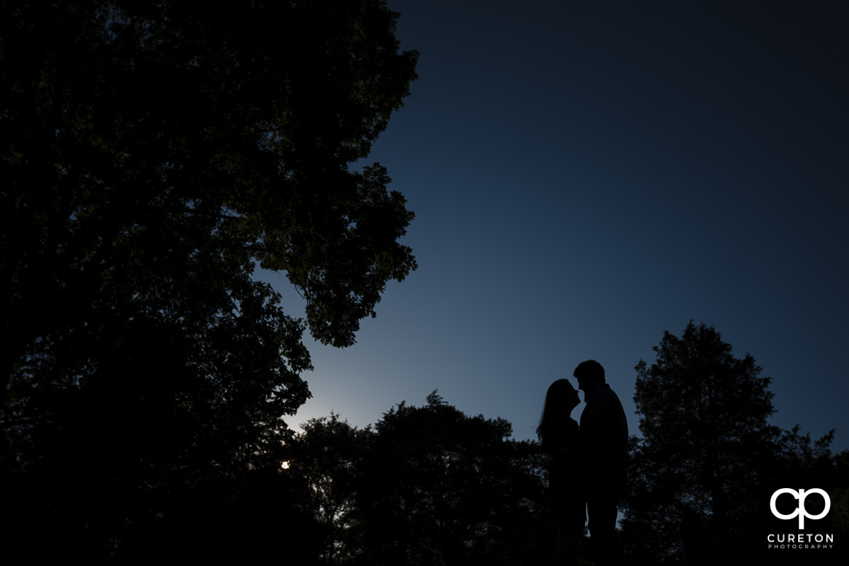 Silhouette of an engaged couple behind a blue sky during a summer engagement session in Greer,SC.