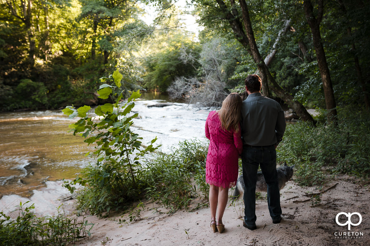 Engaged couple and their dog looking out at the river.
