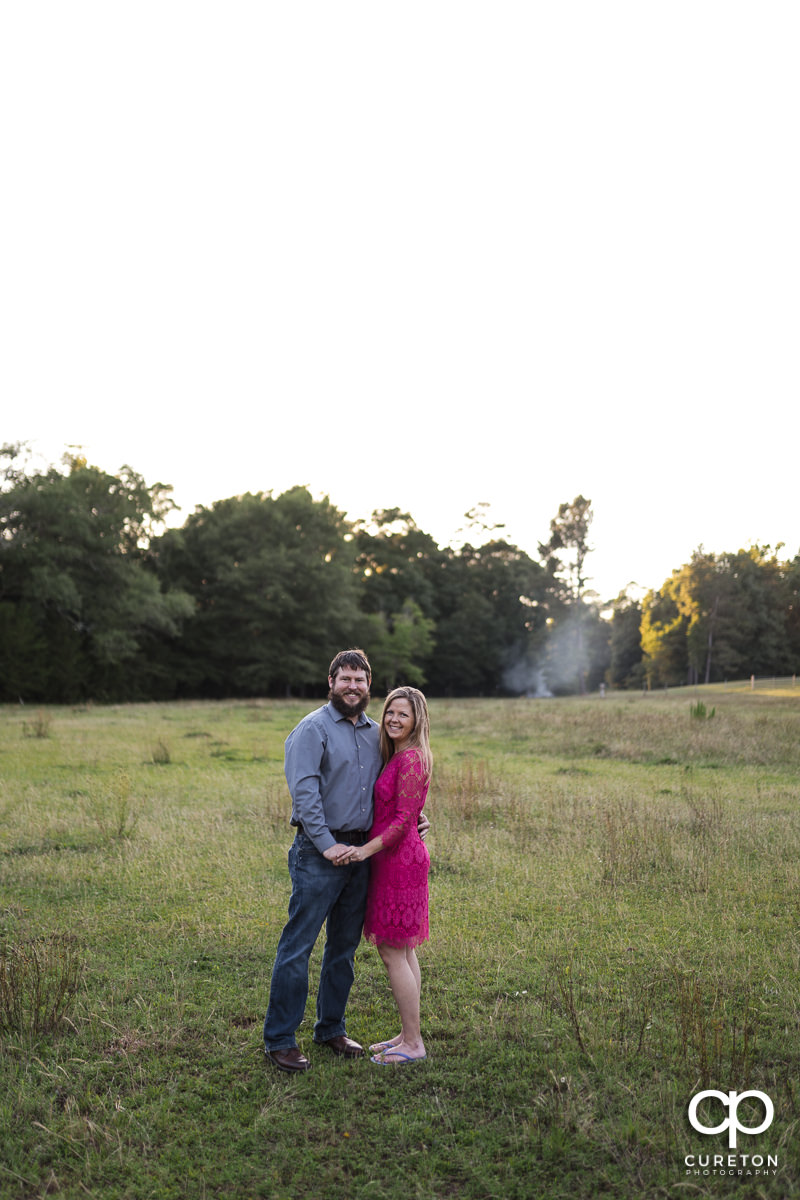 Woman standing in a field with her future husband during a summer engagement session in Greer,SC.