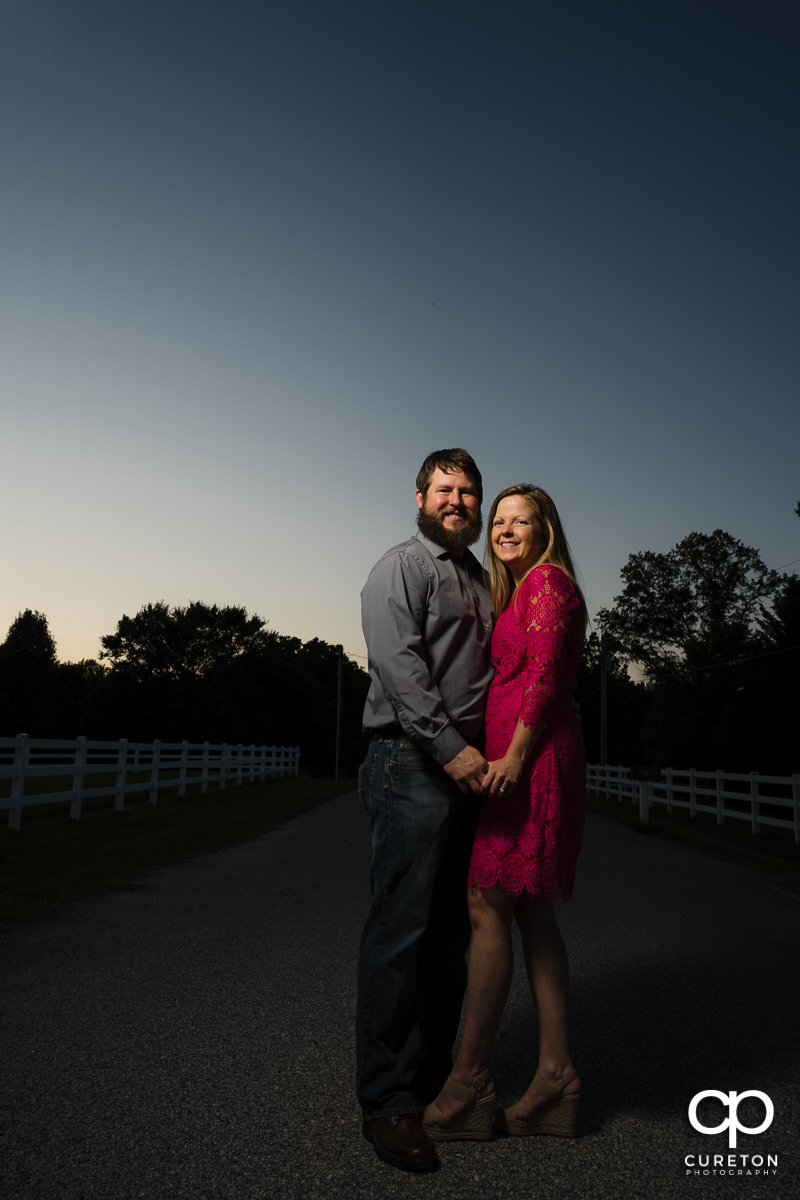 Engaged couple standing in the middle of the road during a summer engagement session in Greer,SC.