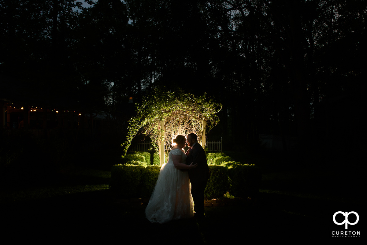 Bride and groom in front of an archway at night at their Grove at Pennington wedding in Greer,SC.