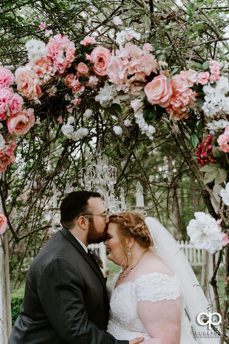 Groom kissing his bride on the forehead underneath a floral arch after their Grove at Pennington wedding in Greer,SC.