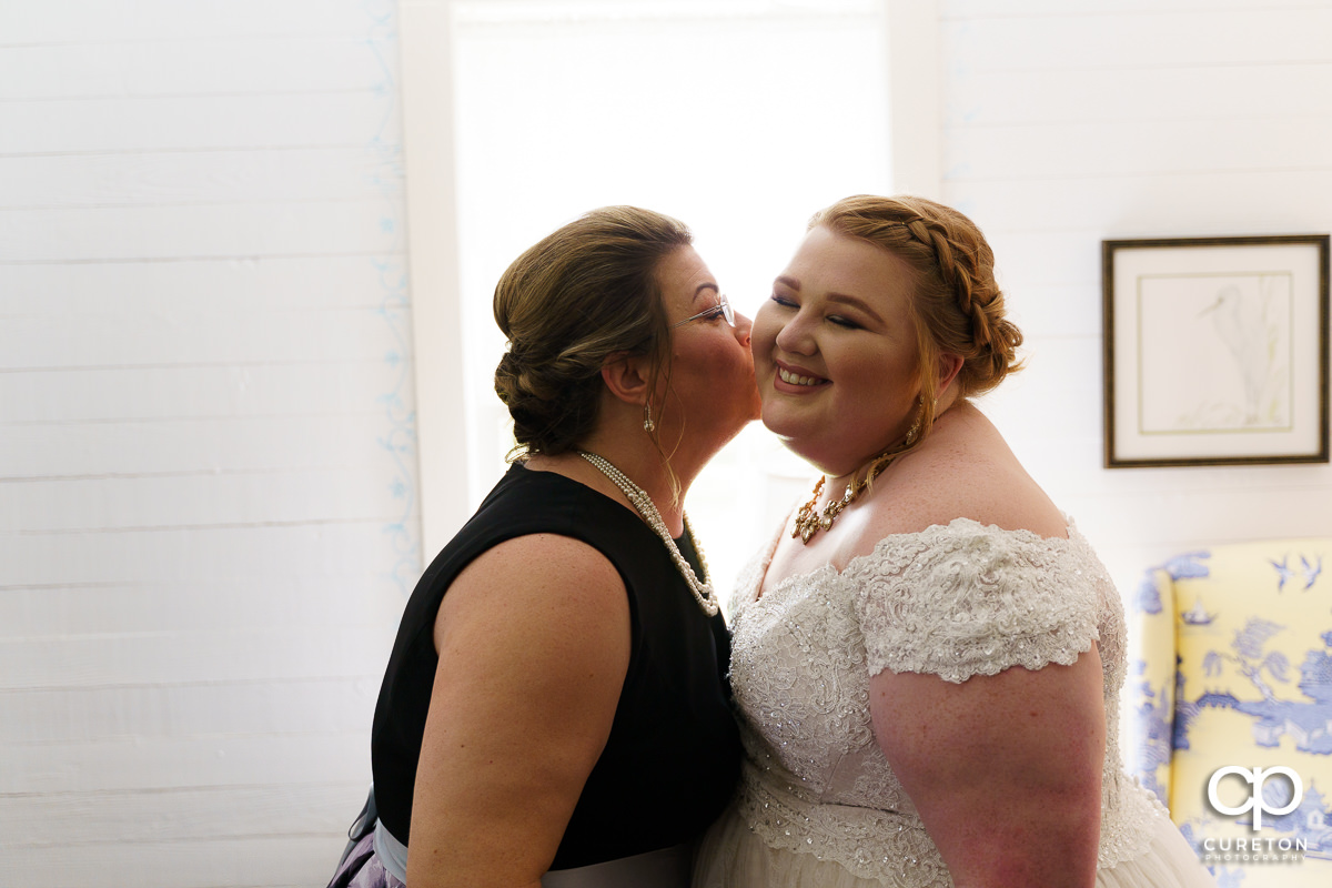 Bride'a mom kissing her on the cheek before the wedding ceremony at The Grove at Pennington.