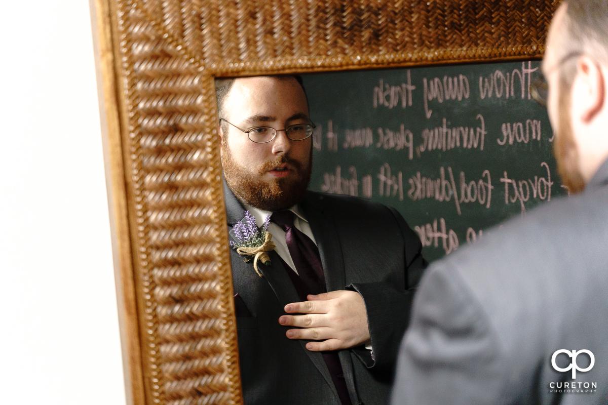 Groom looking in the mirror.