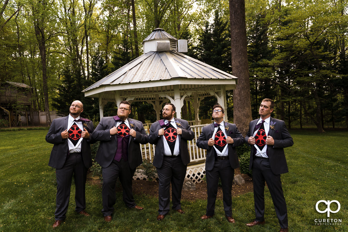Groomsmen opening their formal shirts to reveal Star Wars imperial shirts.