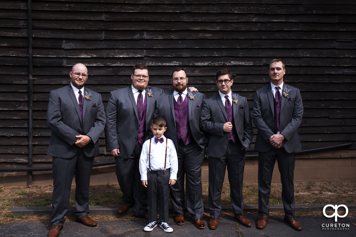 Groom and groomsmen in front of a barn.