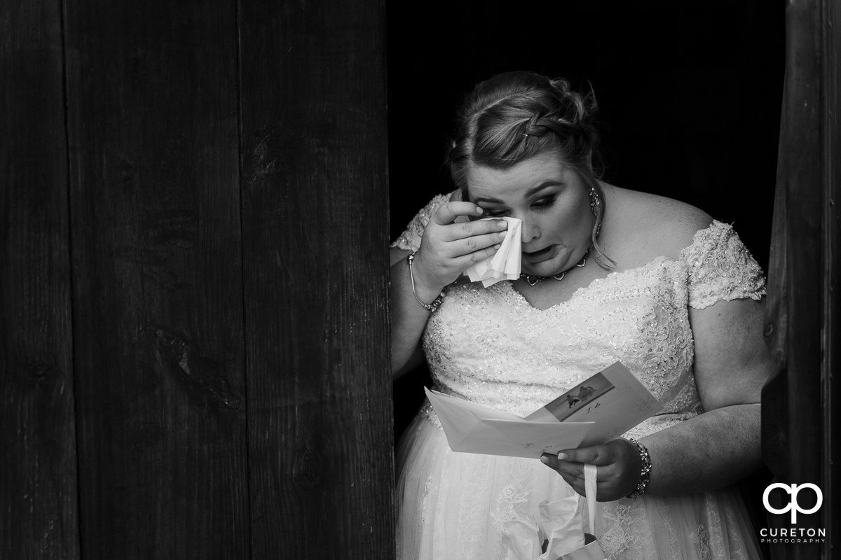 Bride crying reading a letter from the groom.