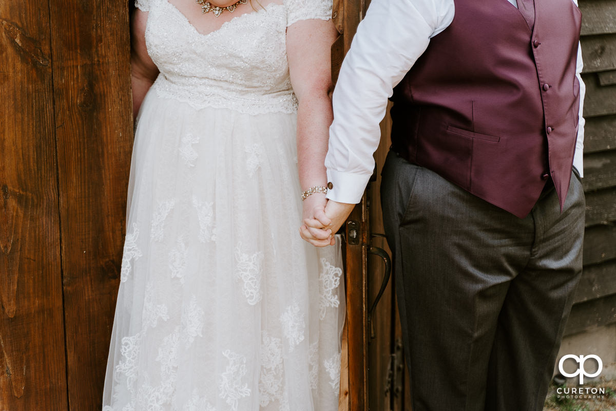 Bride and groom holding hands on the opposite sides of a door.