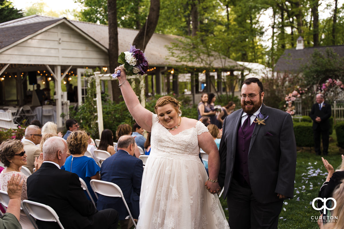 Bride holding her arm in the air as they walk back down the aisle at the Grove at Pennington wedding.