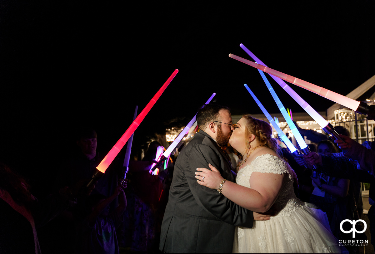 Bride and groom kissing with the wedding party holding light sabers over them.