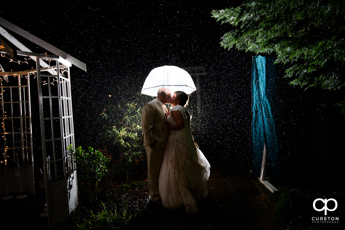 Bride and groom kissing underneath an umbrella in the rain after their Grove at Pennington wedding.