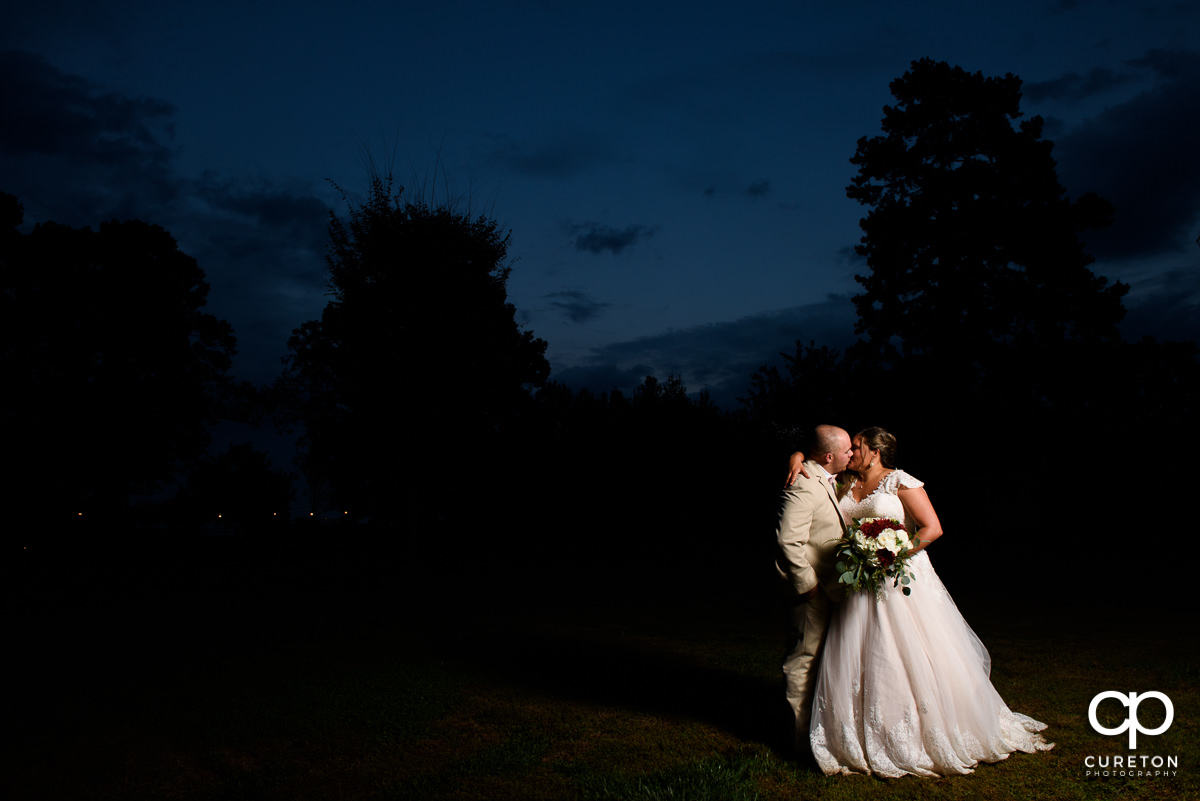 Bride and groom kissing at sunset during their wedding at The Grove at Pennington.