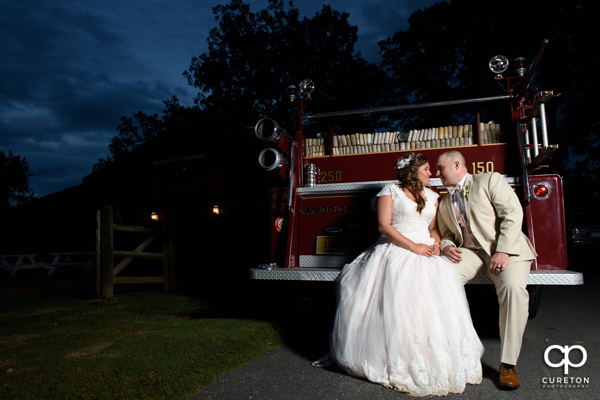 Bride and groom sitting on the rear deck of a fire truck.