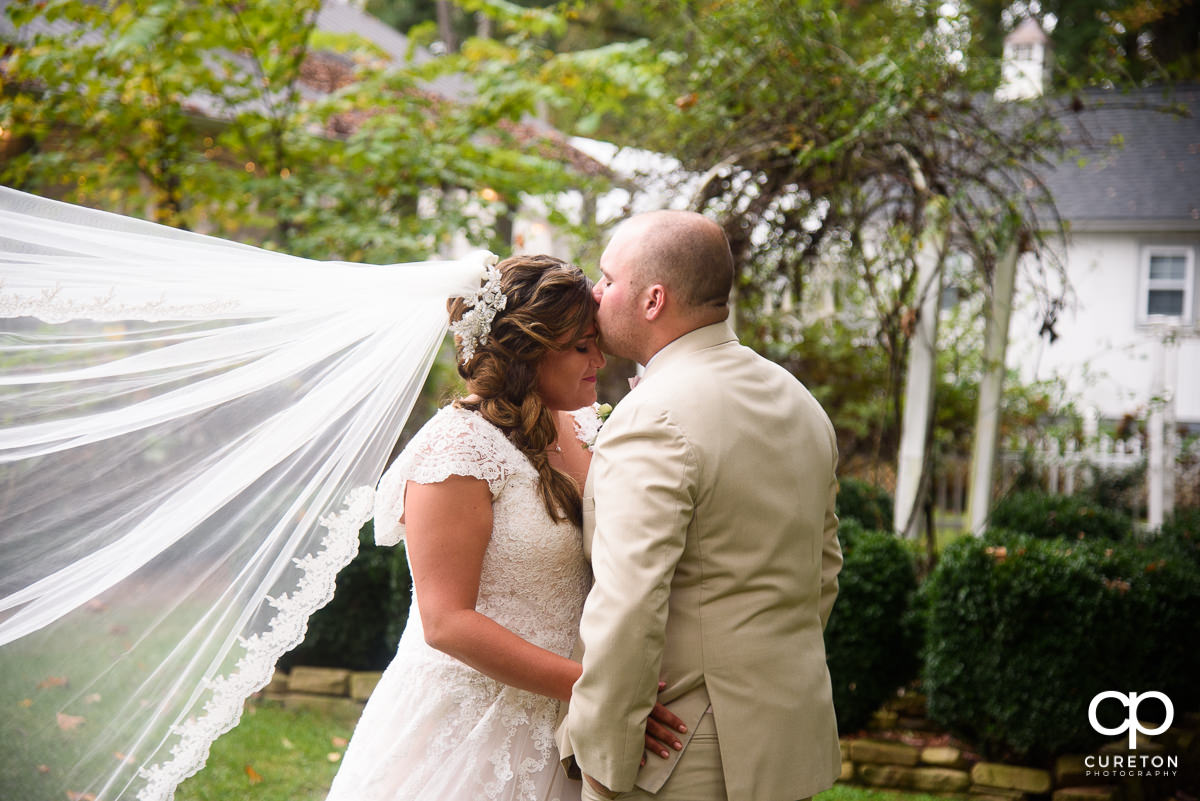 Groom kissing his bride on the forehead with her veil blowing in the wind.