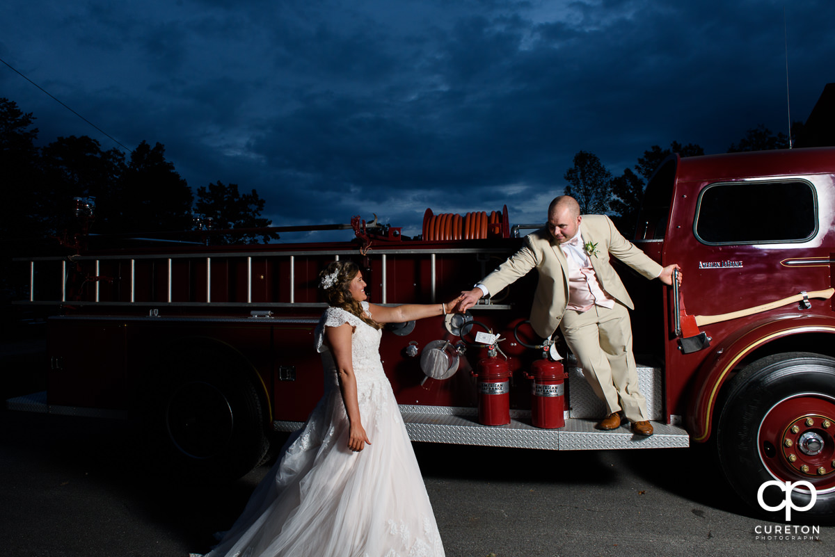 Groom reaching out to his bride while on a fire truck.