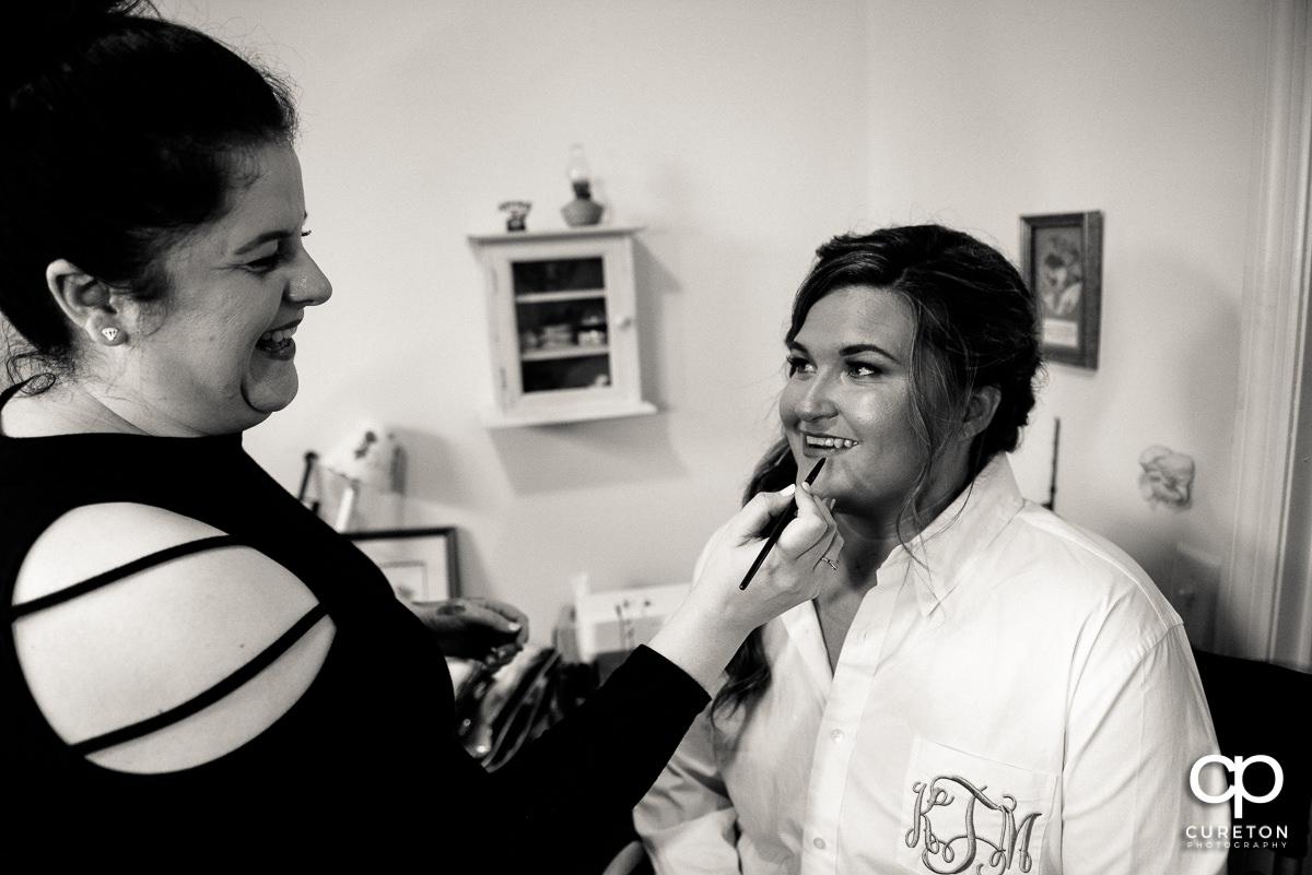 Bride applying lipstick.