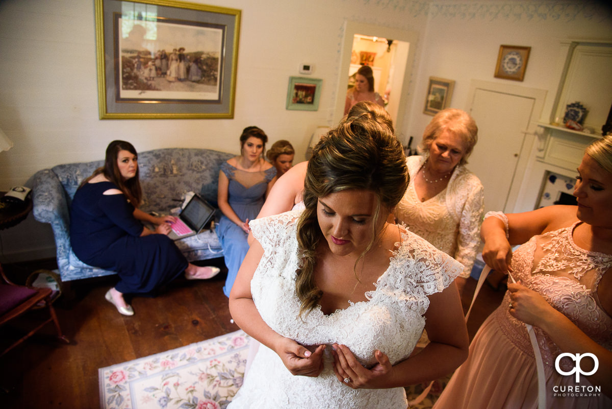 Bride putting her dress on before the wedding.